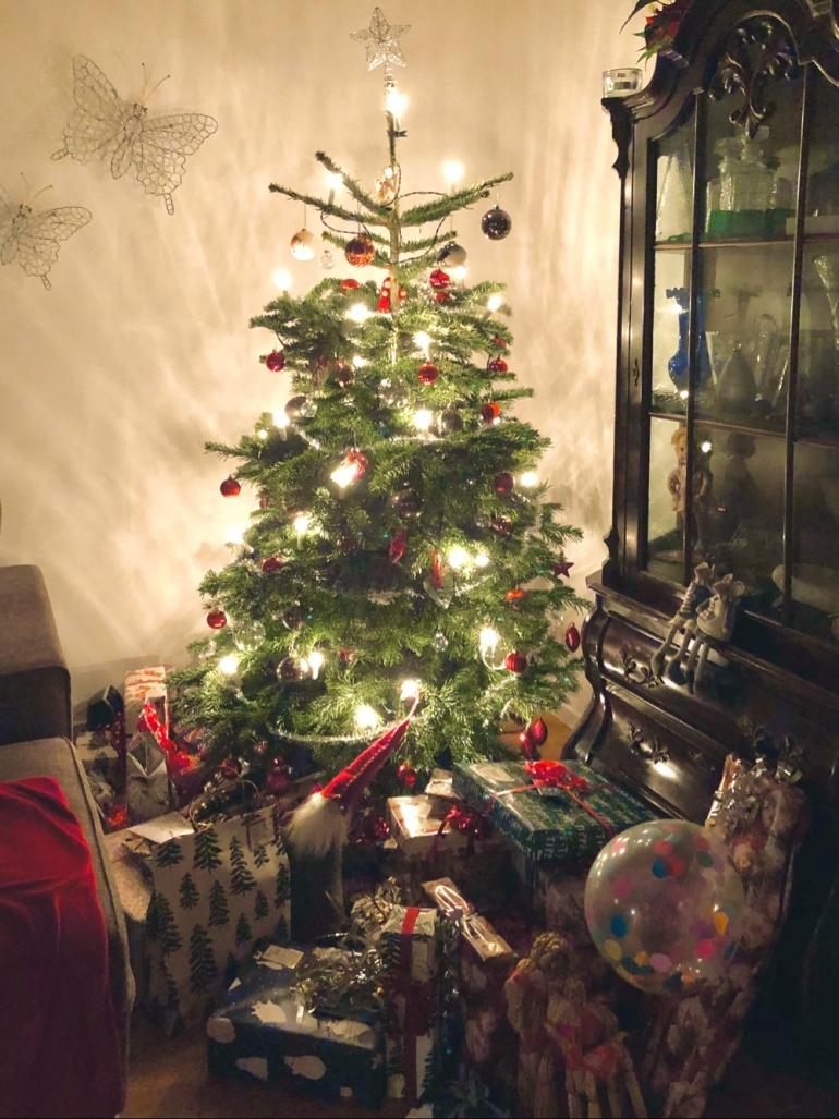 I bilden syns en julgran med massor av presenter i olika storlekar granen är fullt klädd och på väggen sitter fjärils dekorationer av sebastian thorell