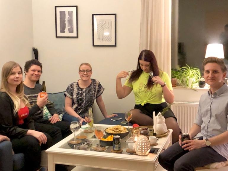 bild på en gäng kompisar runt ett soffbord med chips och drinkar av sebastian thorell