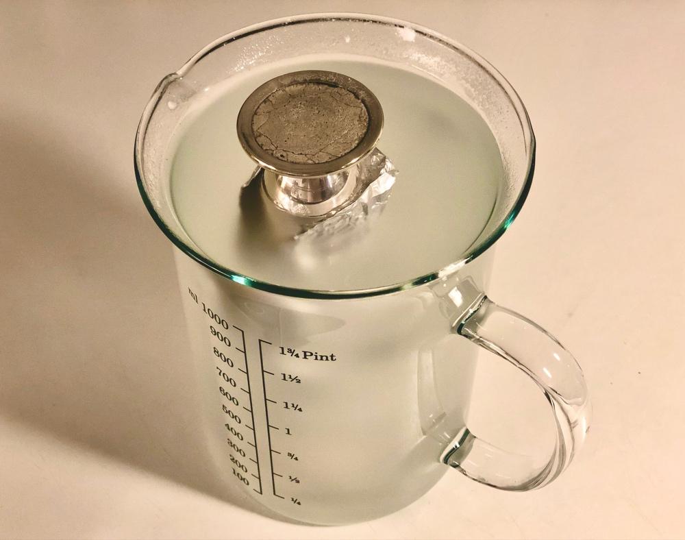 en orkidévas inlindad i folie i en glasbägare med vatten av sebastian thorell