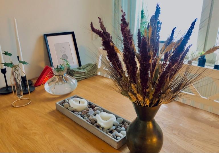 I bilden syns en bukett med torkad lavender och vete i en vas ljus murgröna i vatten servetter och en tavla av sebastian thorell