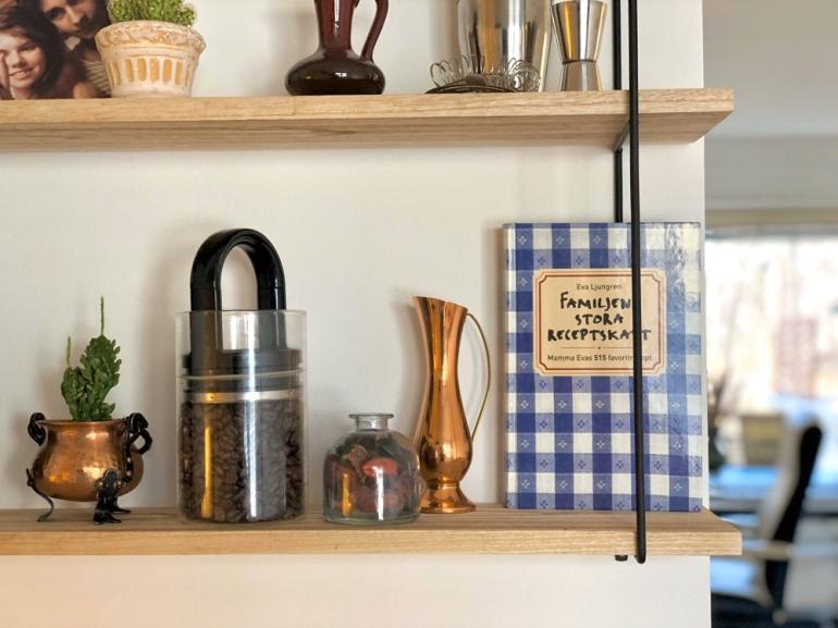 bild på en hylla där det står en kaktus kaffebönor recept bok och en orkidevas av sebastian thorell