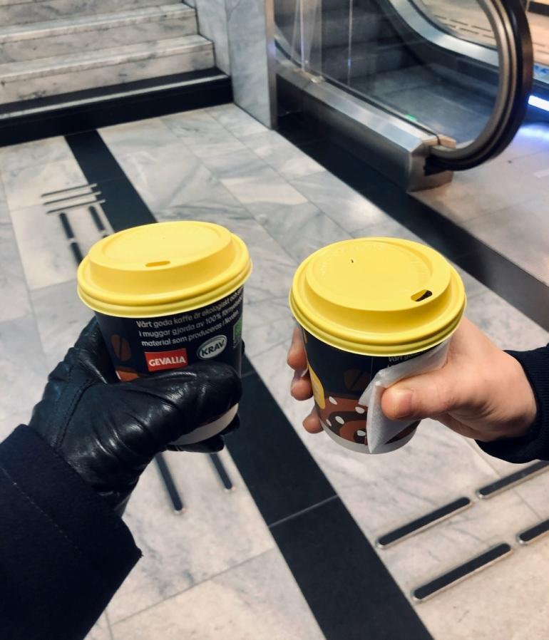 bild där man ser en trappa och en rulltrappa i bakgrunden två händer som håller i kaffekoppar från pressbyrån av sebastian thorell