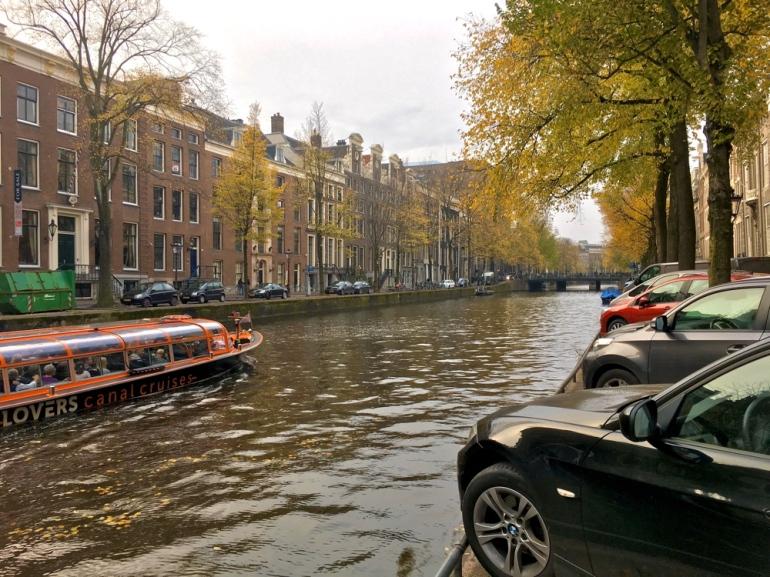 bild på en kanal i amsterdam när en båt åkerförbi av sebastian thorell