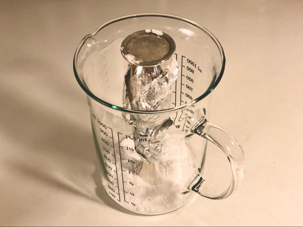 en orkidévas som är inlindad i folie i en glasbägare av sebastian thorell