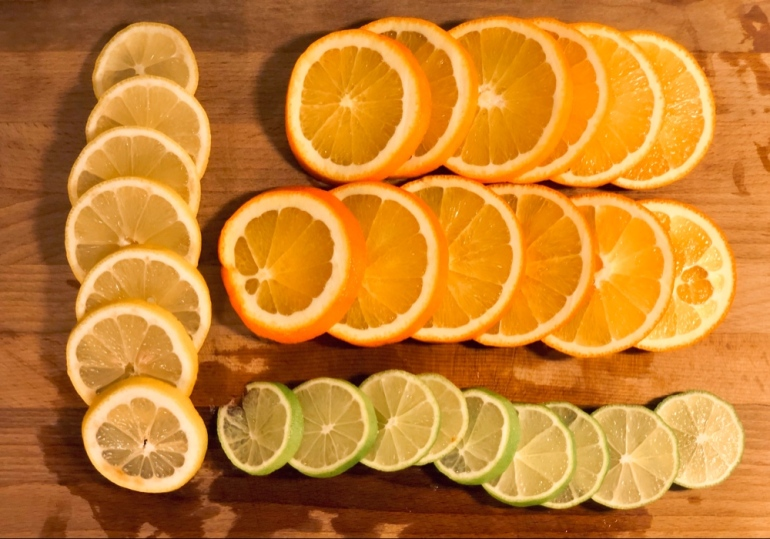 en bild där man ser skivad apelsin citron och lime ligga uppradat på en trä skärbräda av sebastian thorell