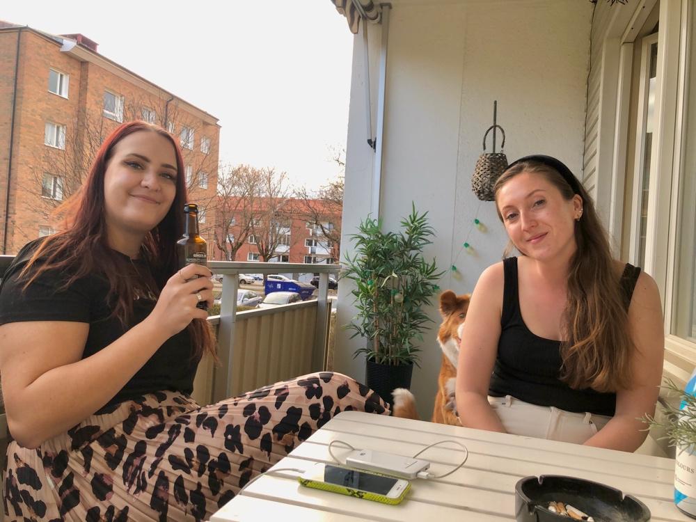 bild på två tjejer som sitter och dricker öl på en balkong av sebastian thorell
