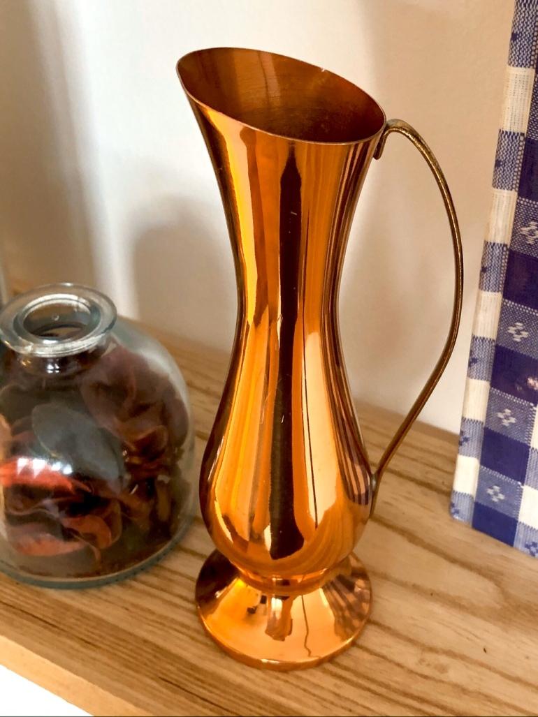 närbild på en orkidevas i koppar och en glasburk med torkade rosblad av sebastian thorell