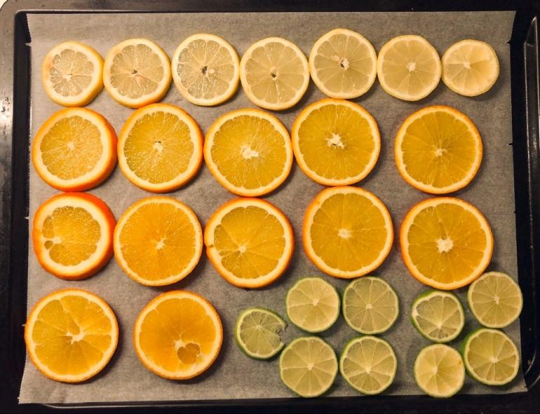 på bilden ser man skivade apelsin citron och lime på bakplåtspapper i en plåt