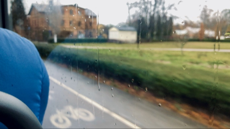 Bild från en buss man ser utsidan en gång och cykelväg och regn på buss fönstret av sebastian thorell