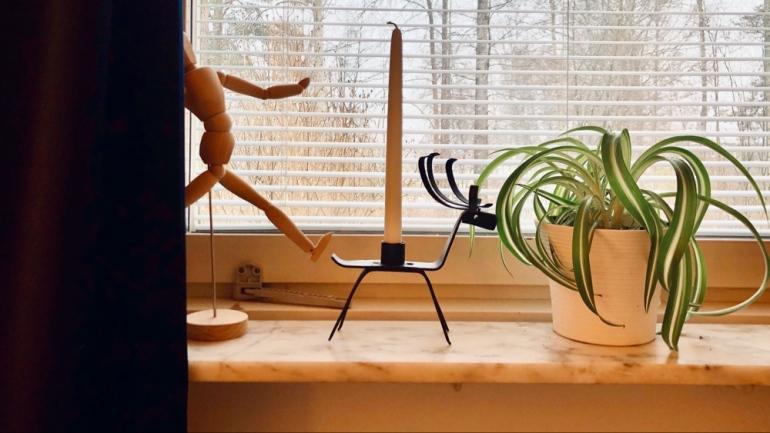 Bild på ett fönster med gardin där en ljustake i form av en ren och en ampellilja