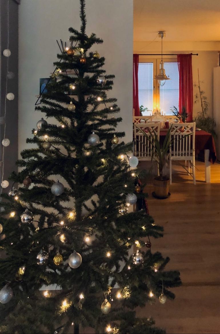 bild på julgran med silver och guld julgrans kulor i bakgrunden ser man ett matbord av sebastian thorell