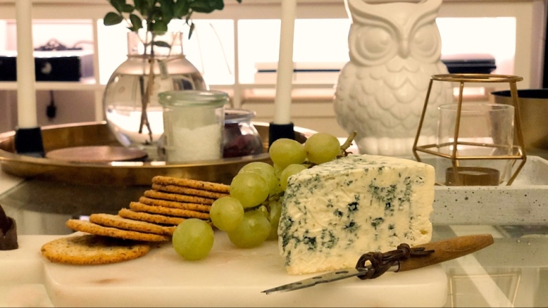 i bild syns en ostbricka med möggelost kex och vindruvor av sebastian thorell