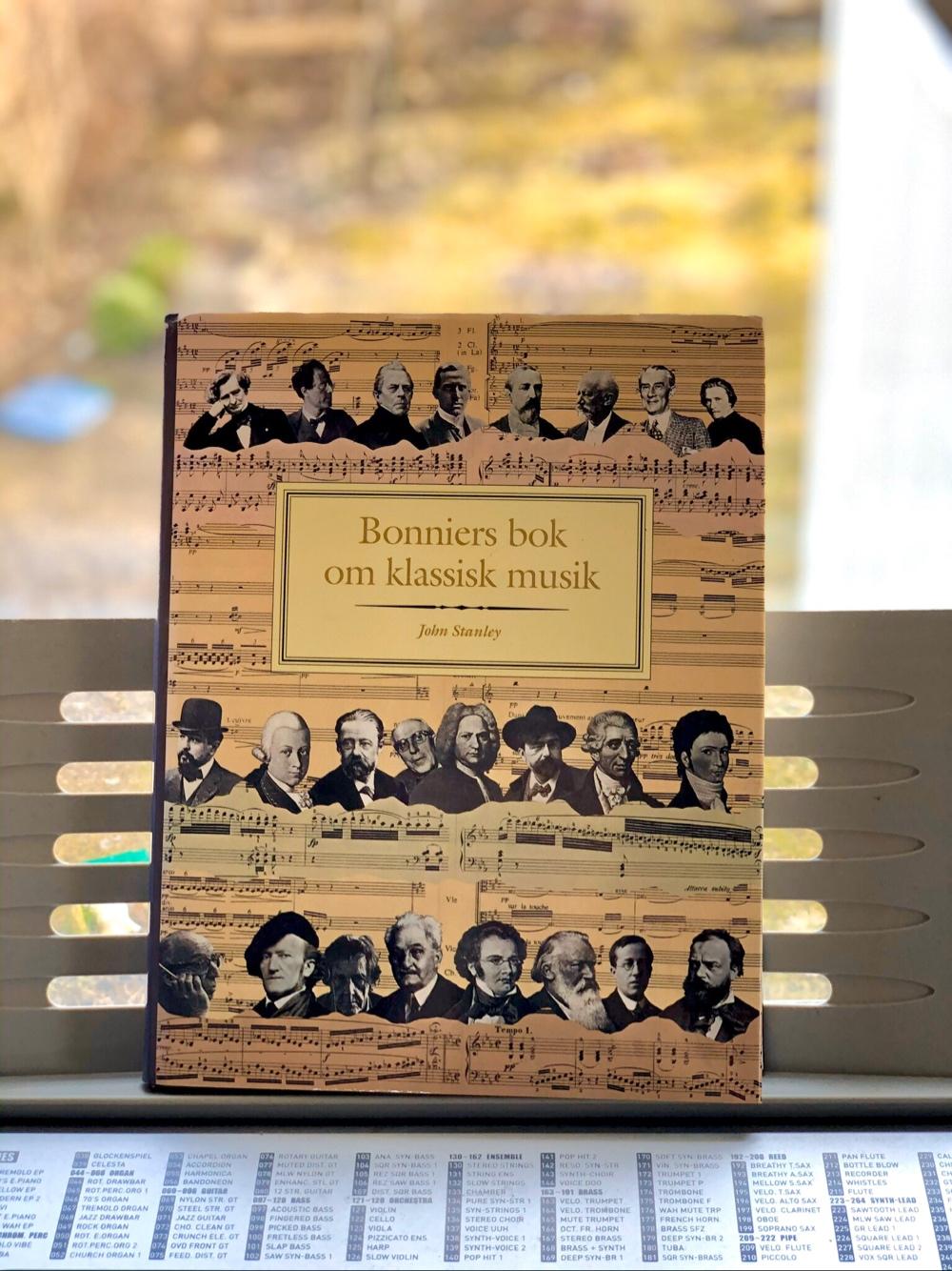 på ett keyboard står en bok som heter bonniers bok om klassisk musik av sebastian thorell