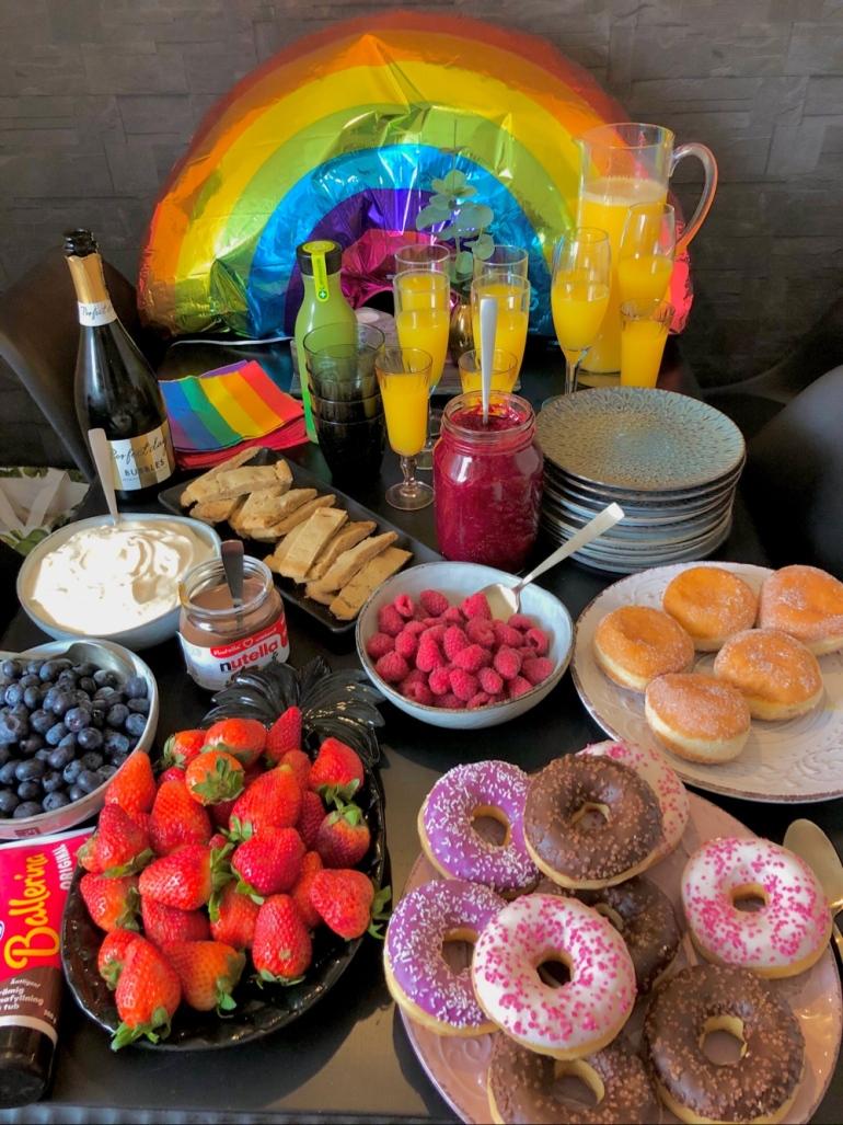 bild på ett bord med upplagda godsaker som munkar jordgubbar hallon kakor nutella mimosa