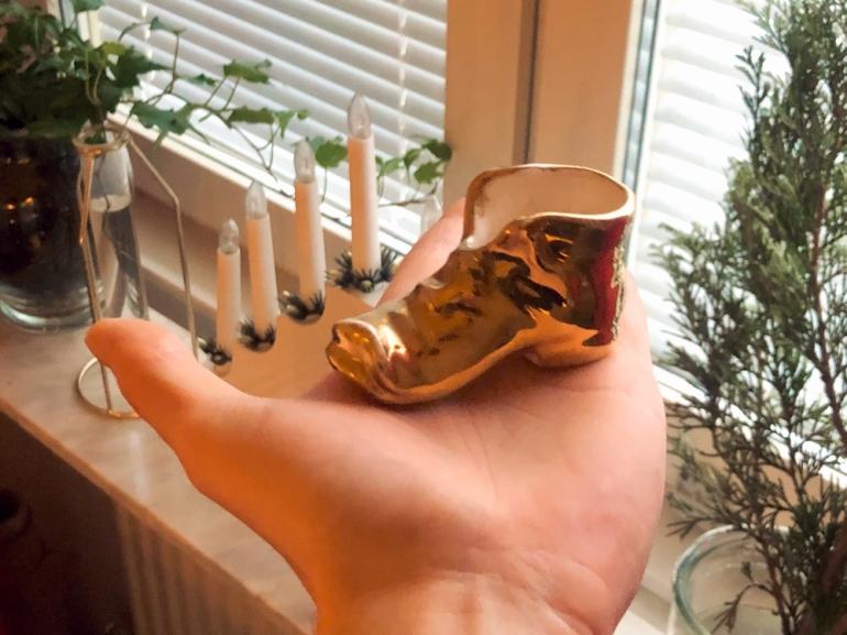 i bild syns en hand som håller upp en liten guldsko framför ett fönster av sebastian thorell