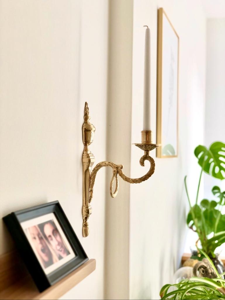 bild med fokus på en detaljrik vägg ljusstake i guld av sebastian thorell