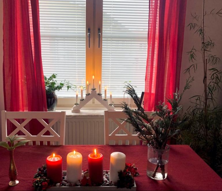 I bilde syns ett fönster med röda gardiner och en ljusstake och framför står ett matbord med en rödbordsduk granris adventstake av sebastian thorell