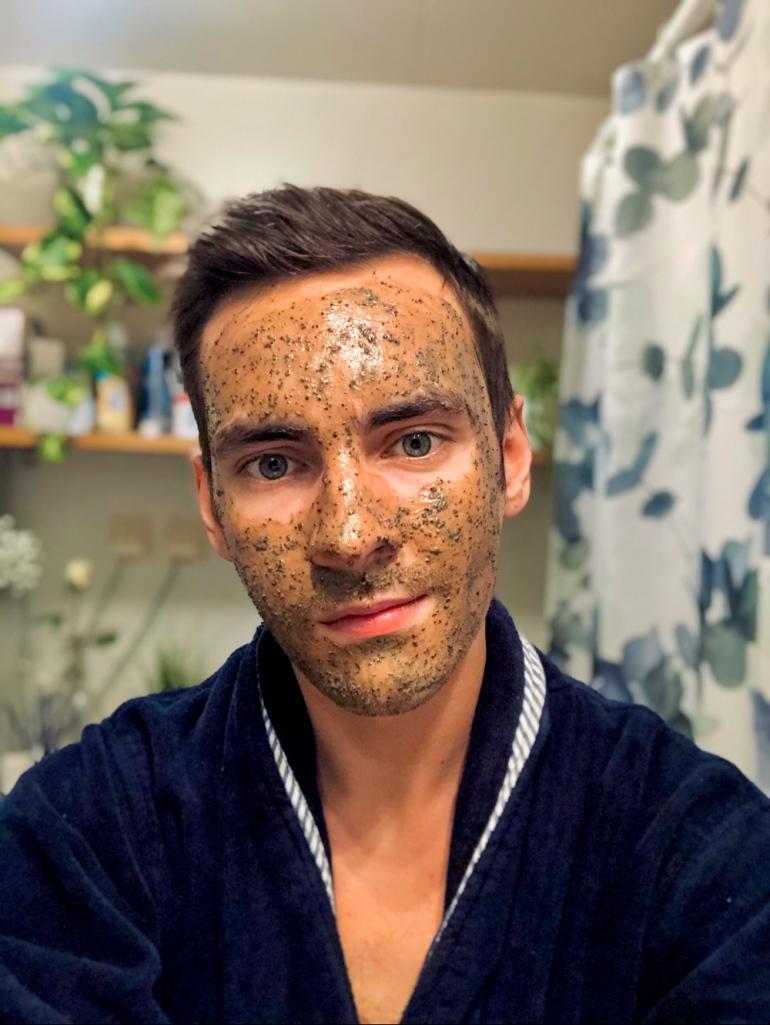 I bild ser man en kille med en ansiktsmask gjord på kaffe han har mörblå morgonrock på sig på och av sebastian thorell