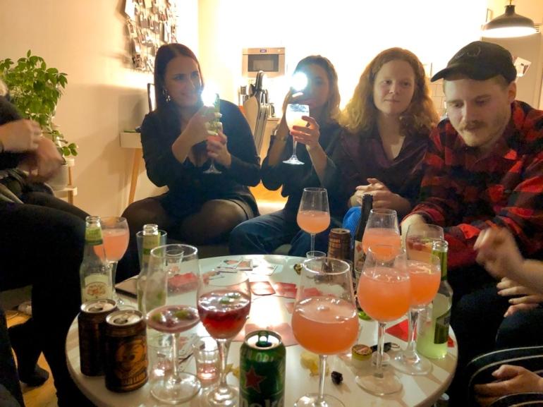 bild på fest där männsikor sitter runt ett soffbord spelar kort och dricker drinkar av sebastian thorell