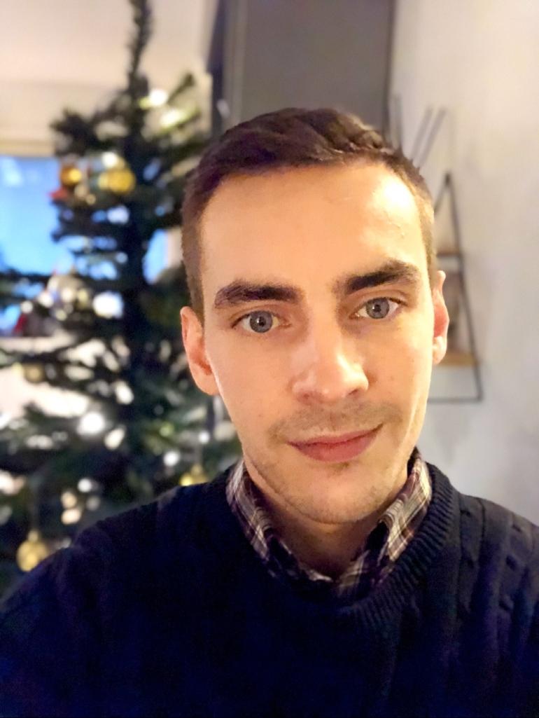 En selfie av sebastian thorell framför en julgran