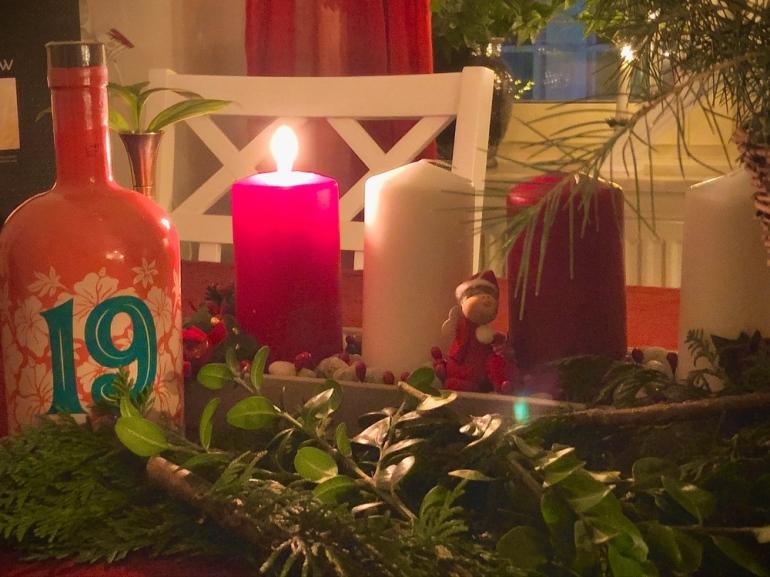 Närbild på blossa glögg och adventsljusstake där första ljuset är tänt med kvistar framför av sebastian thorell