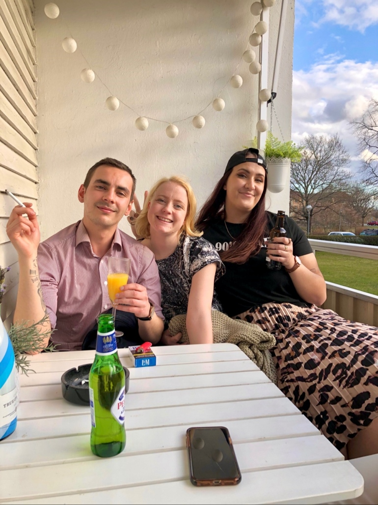 bild på tre glada personer som sitter i solen på en balkong och dricker öl och mimosa
